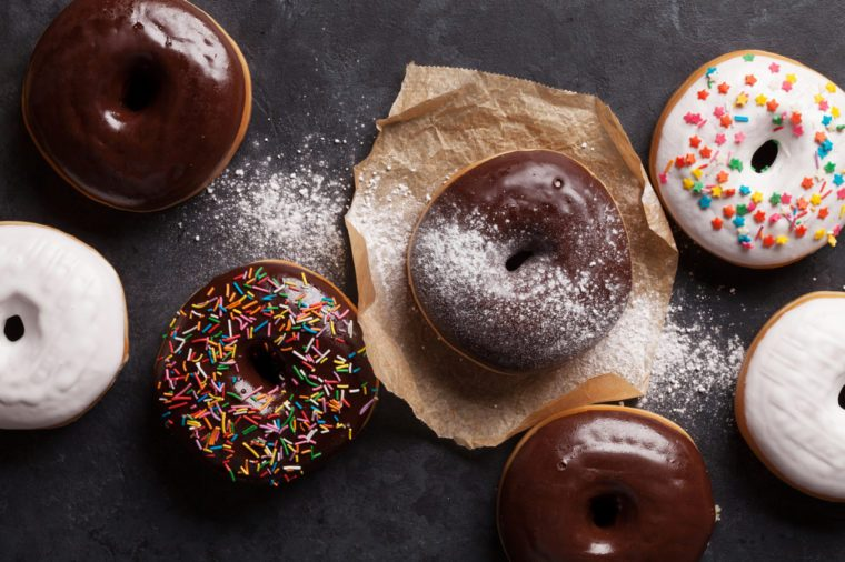 Colorful donuts on stone table. Top view