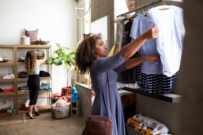 Mixed race female customer clothes shopping in a boutique