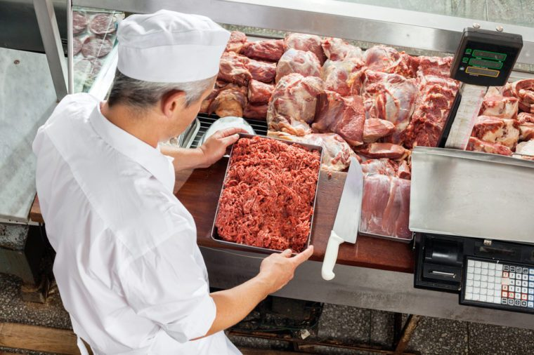 High angle view of butcher holding minced meat tray at display cabinet in butchery