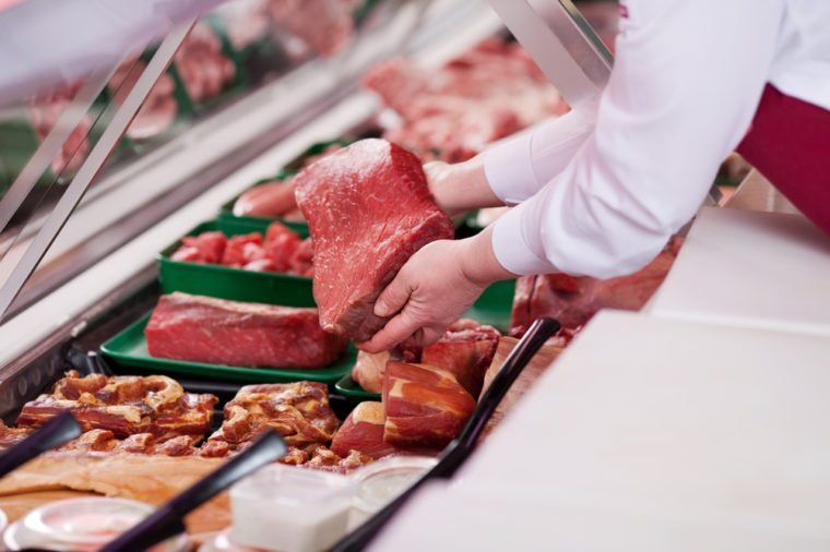 saleswoman offering fresh meat at display in supermarket