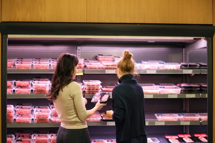Women purchasing a packet of meat at the supermarket