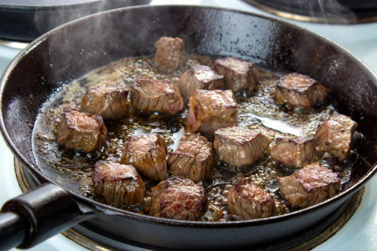 Frying beef bottom round roast cubes in cast iron skillet , meat flipped once