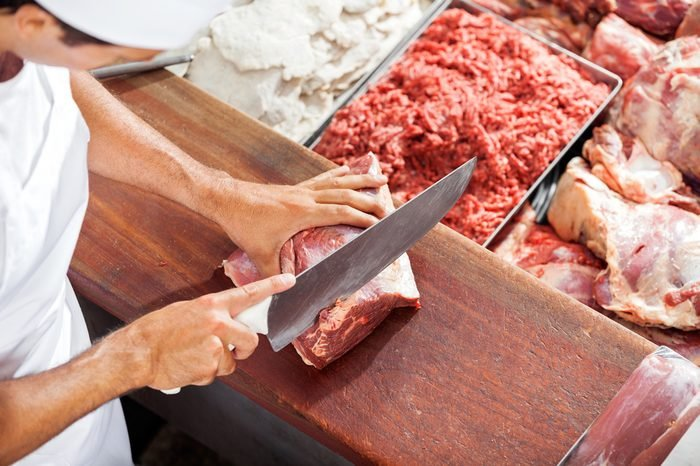 High angle portrait of smiling butcher cutting meat at counter in butchery