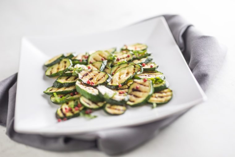 Grilled zucchini with red spice on white plate.