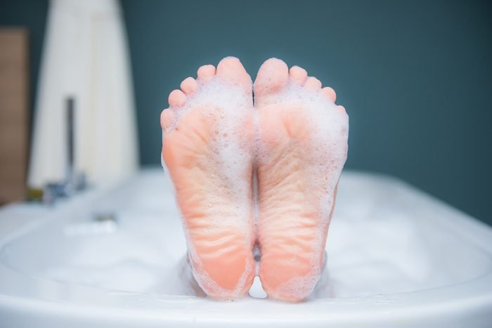 Closeup of woman's foot on the edge of a bath with foam, care