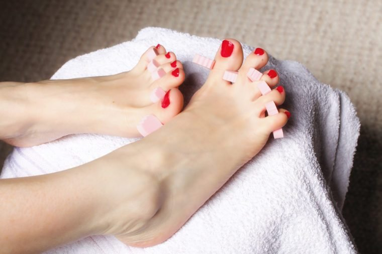 foot pedicure applying woman's feet with red toenails in toe separators