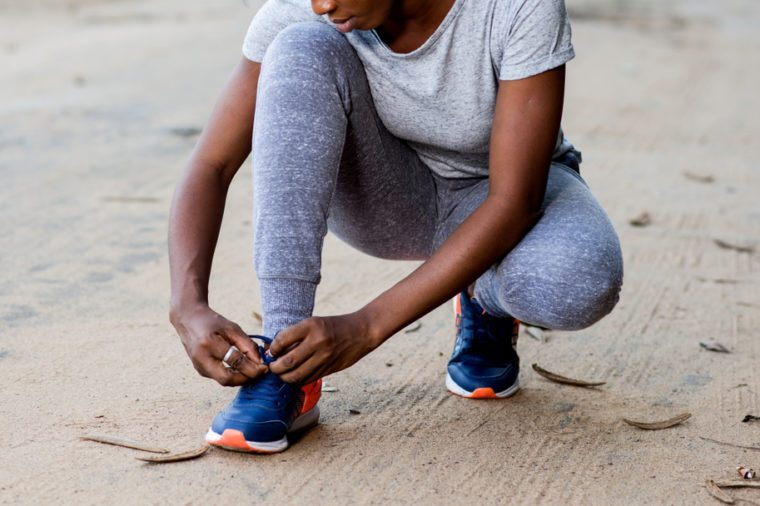 young girl in sportswear squatting on a track and ties her laces for sport.