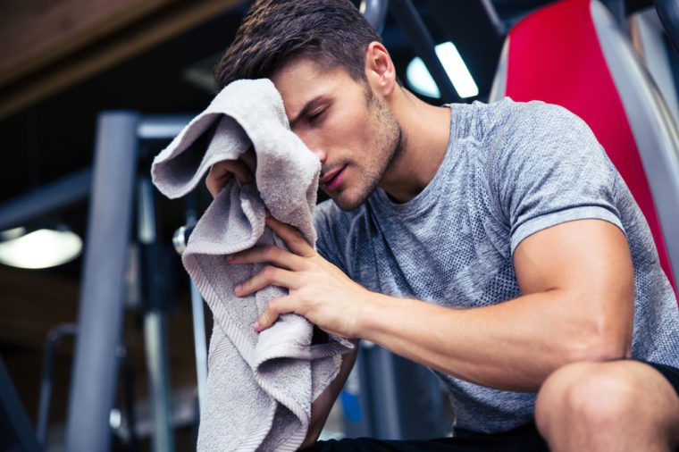 Portrait of a handsome man sitting on the bench with towel in fitness gym