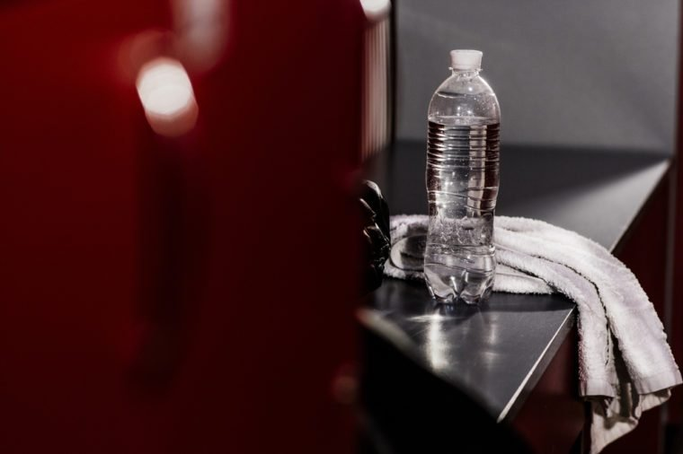 In the locker room of the gym. White towel boxing gloves, a bottle of water. advertising water. Accessories athlete. After a workout. Advertising Sports Club. Motivation to sport.
