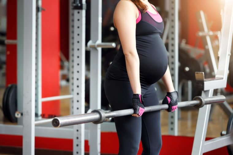Pregnant woman exercising in the gym. Fitness and healthy lifestyle during pregnancy. Pregnant girl with a big tummy during the third trimester goes in for sports.