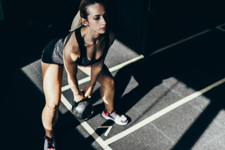 Athletic sportswoman exercising in gym, squatting while lifting up kettlebell