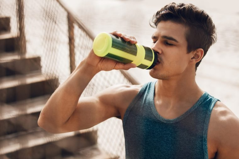 Close up shot of fit young man drinking water by the beach after workout. Runner drinking water after exercising.