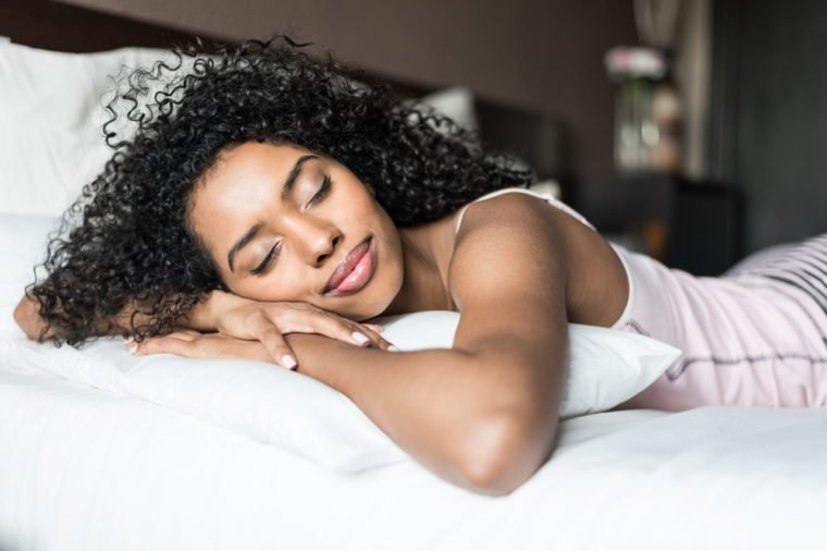 woman happy on bed smiling and stretching looking at camera