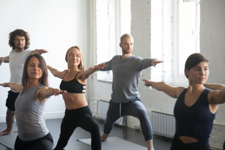 Group of young sporty attractive people practicing yoga lesson with instructor, standing in Warrior Two exercise, Virabhadrasana 2 pose, working out, indoor close up image, studio. Wellness concept