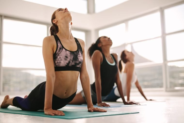 Young women practicing yoga. Fitness women meditating while doing cobra pose in gym.