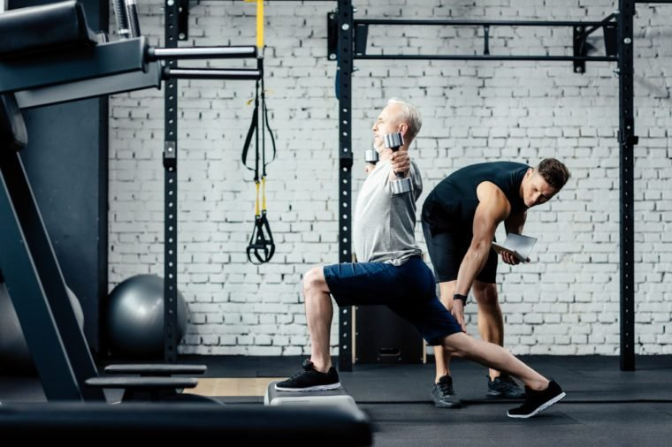 senior sportsman doing lunges with dumbbells in sport center with trainer near
