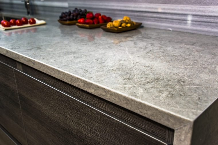 stone gray worktop with dark kitchen cabinets, granite countertop over modern kitchen cabinets with blue motion without handles