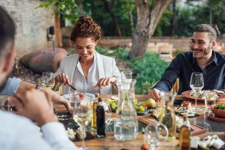 Group of men and women enjoying outdoor dinner celebration.
