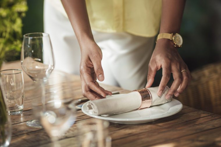 Hands of cropped unrecognizable African woman putting cutlery on terrace dinner table.