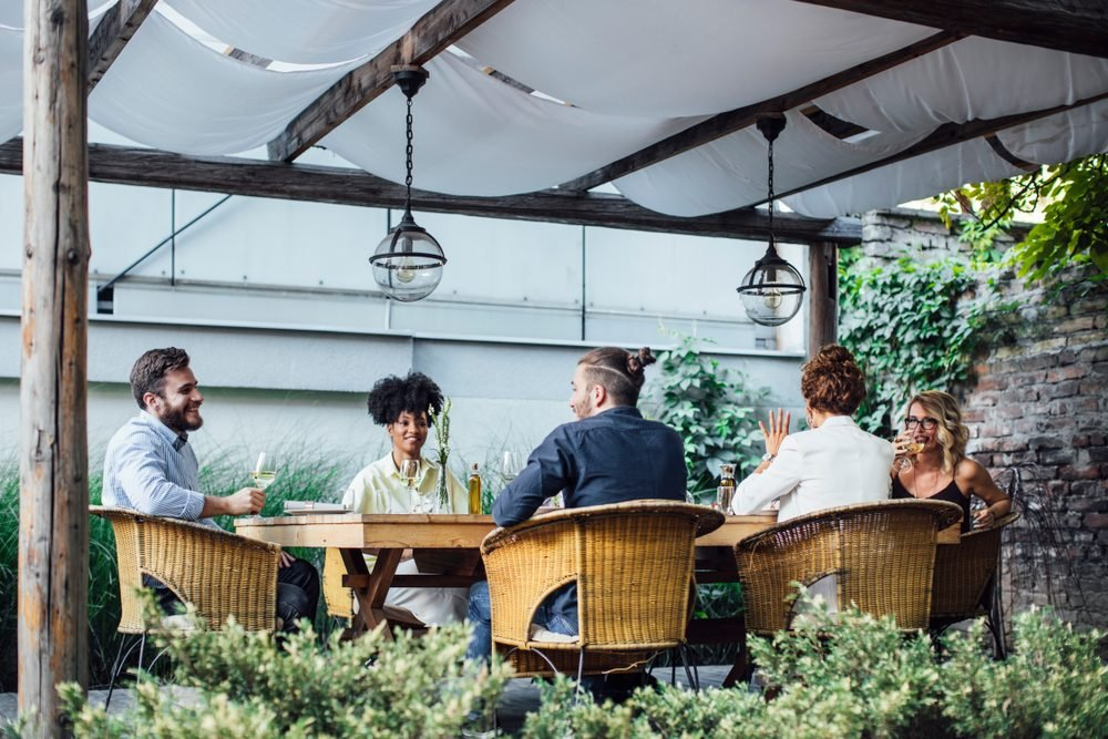Multiethnic group of smiling people sitting outdoor and having fun time on dinner party celebration.