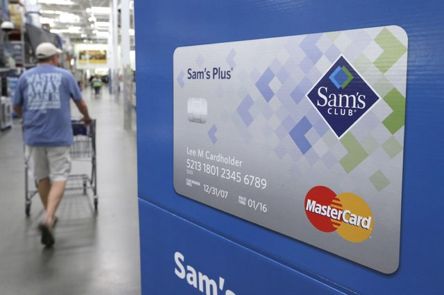 A customer walks past a sign promoting Sam's Club MasterCard credit cards at a Sam's Club store store in Bentonville, Ark