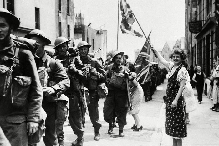 Housewives with Union Jacks, wave to some of the men, all Canadians, when they marched from the docks after disembarking on