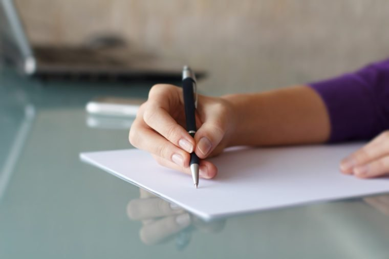 Businesswoman writing with pen