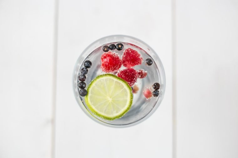 Top view of a refreshing Gin & Tonic with raspberries, lime, blueberries, pomegranate and dried spiced berries