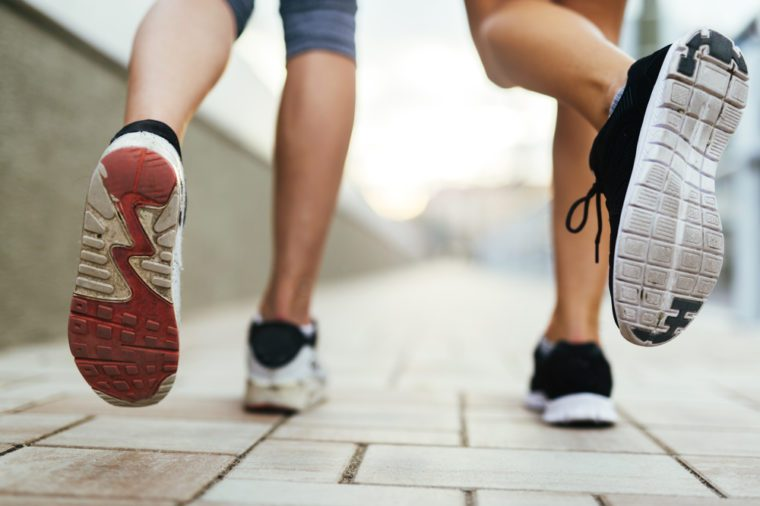 Beautiful women jogging on pavement in city and feets are in focus