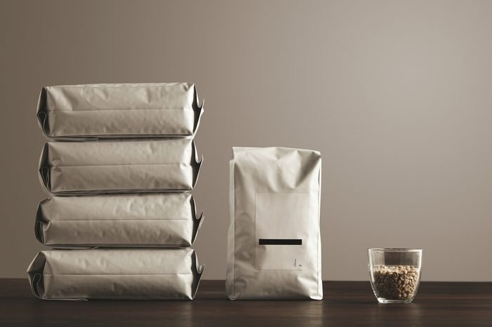 Retail pack: Big hermetic package with blank label presented near other four lying pouches filled with goods, near transparent glass with raw sampled coffee beans on red table, isolated