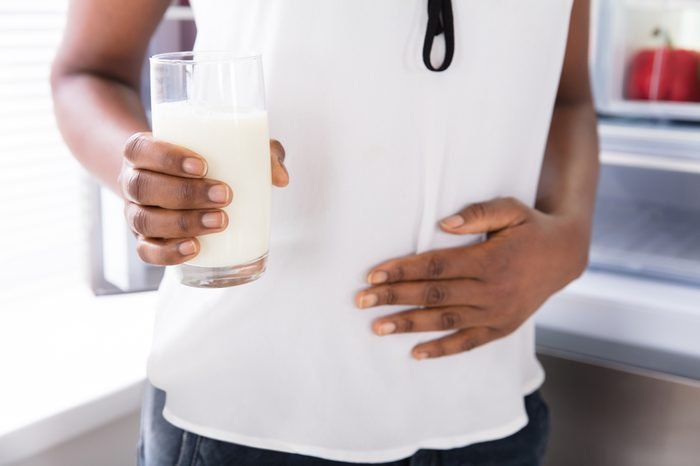Mid Section View Of A Woman With Hand On Stomach Holding Glass Of Milk