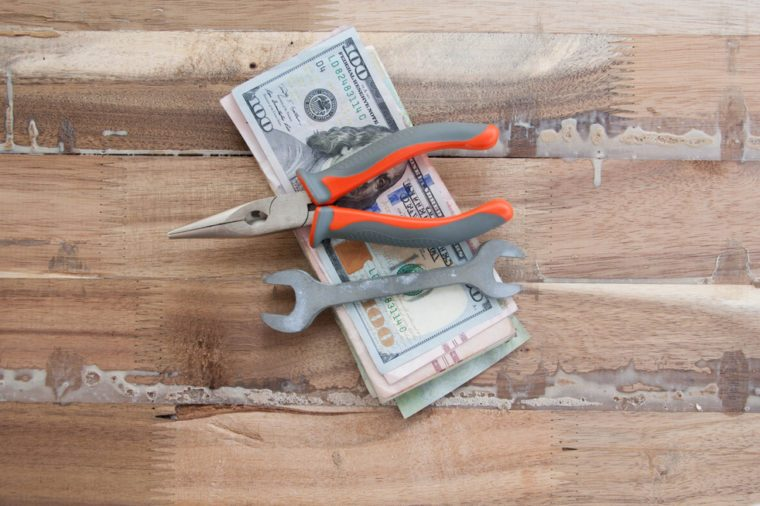Money and worker concept. hundred dollar and tools on wooden table.