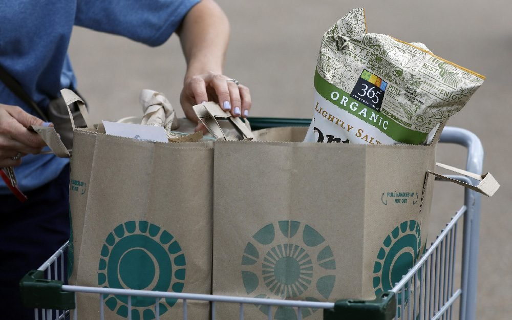A Whole Foods Market customer prepares to remove her purchases from a shopping basket outside the Jackson, Miss., store, . Amazon is buying Whole Foods Market in a deal valued at $13.7 billion, uniting the on-line giant with the grocery store chain that touts fresh organic foods