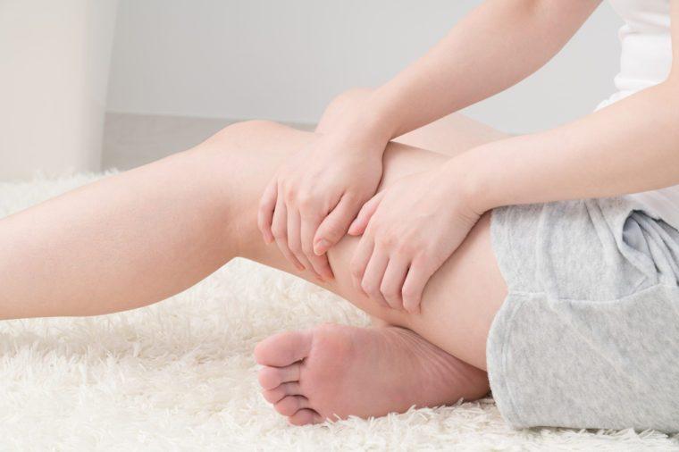 Woman doing self massage, thighs, foot