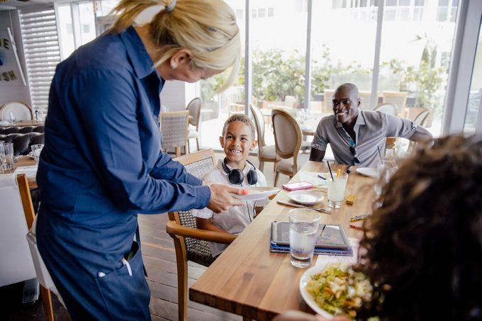 Server Bringing Food For Family In Restaurant