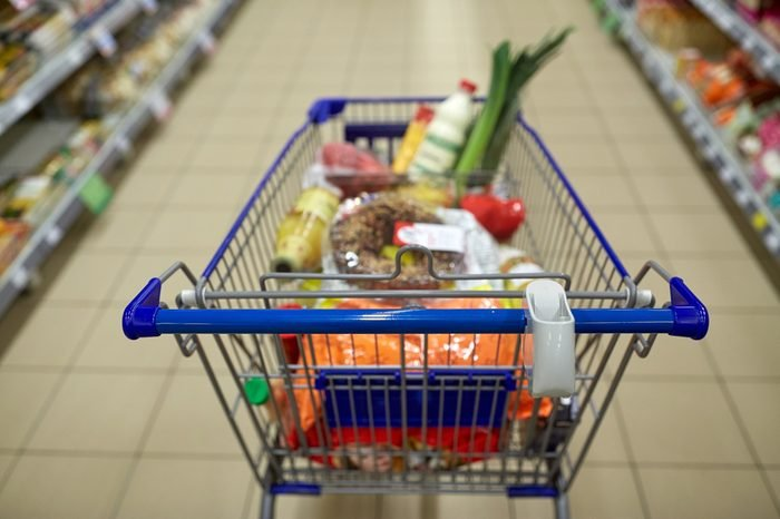 consumerism concept - food in shopping cart or trolley at supermarket