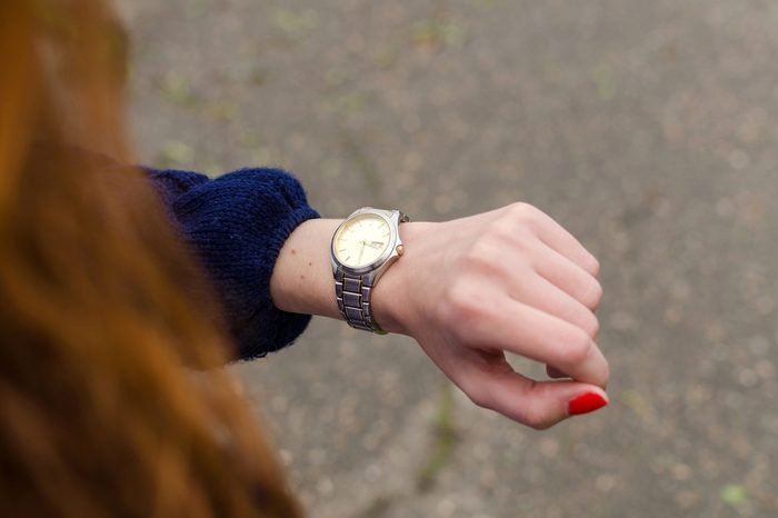 Close up of young woman looking at her hand watch