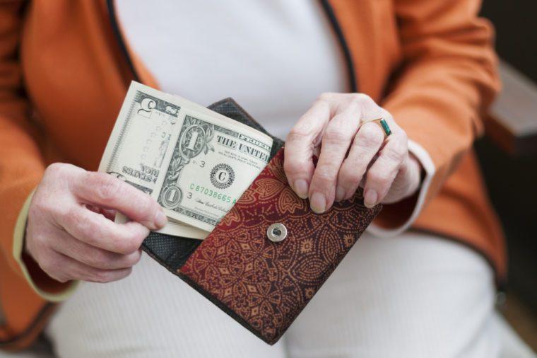 Senior women looks in her purse with US dollar bills.