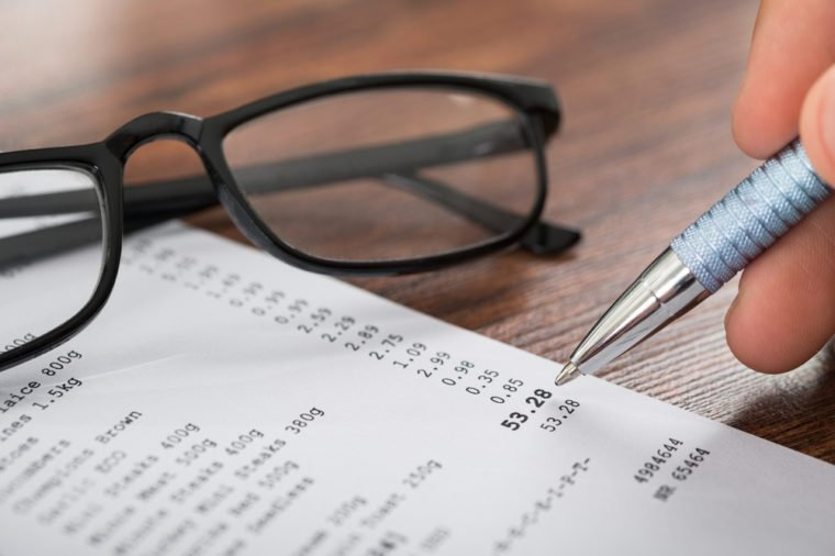 Close-up Of Person Hands Holding Pen Over Shopping Receipt And Eyeglasses