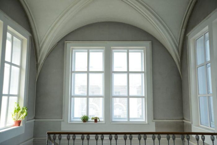 Background of empty big white classical room render with round vault ceiling above rectangular day light windows concrete frame in clear texture gray wall low key backdrop