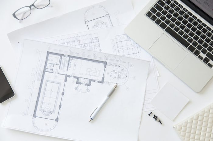Top view of a working desk: laptop, glasses, mobile phone, pen, architect drawing, close up, education concept photo