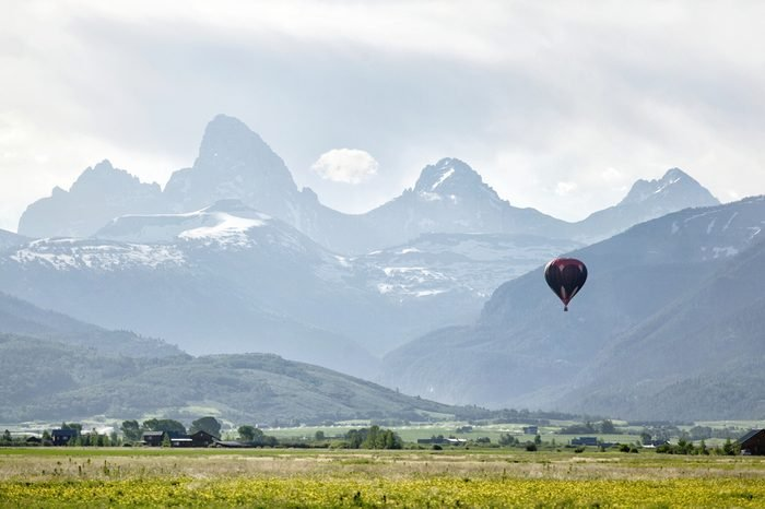 A view of a hot air balloon floating over the Idaho country side, in front of the Grand Teton on a hazy morning.
