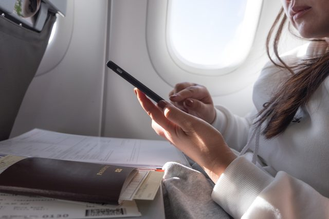 Attractive female passenger of airplane read news from networks via smartphone and wifi on board, young woman sending message on phone traveling by plane in first class connecting to wireless on phone