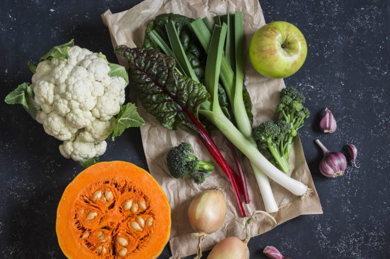 Homegrown harvest - pumpkin, cauliflower, chard, leeks, broccoli, onion, garlic, apple. Autumn vegetables. On a dark background, top view