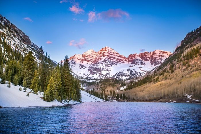 The Rocky Mountains near Aspen, Colorado glow in the light of the morning sunrise, as the mountains and trees reflect off the lake.