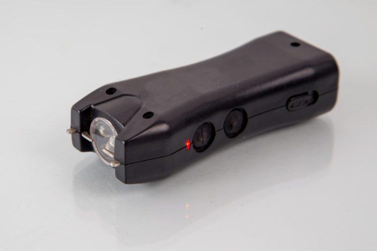black plastic stun gun with flashlight , closeup