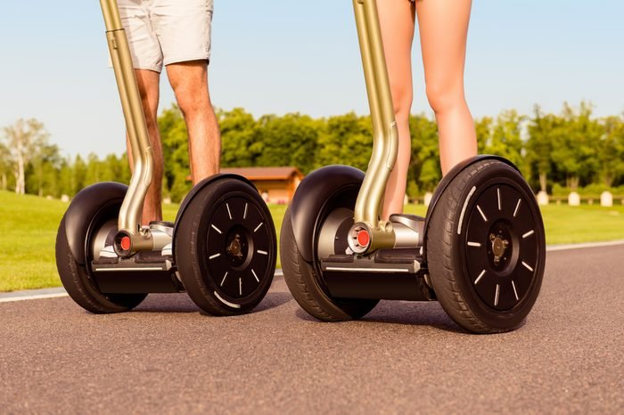 Close up photo of two people riding electric segways