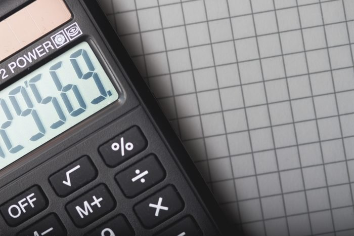 handheld calculator is lying on sheet of paper