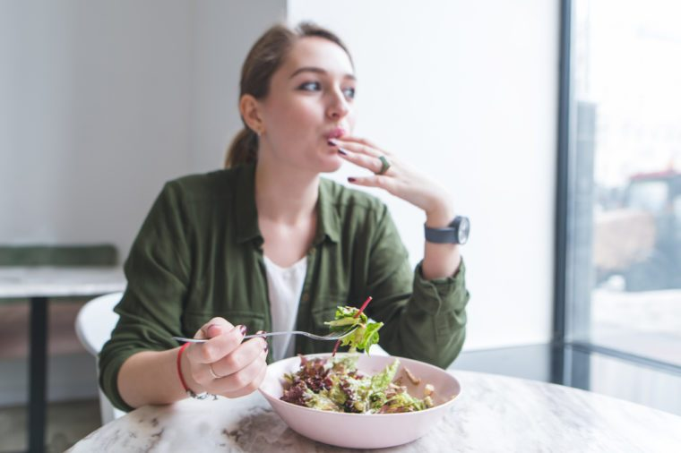 Beautiful young woman eating salad in a restaurant and looking in the window. Focus on a salad plate. Lunch with a healthy meal at the restaurant