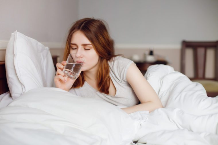 Young healthy girl drink water in her bed on morning